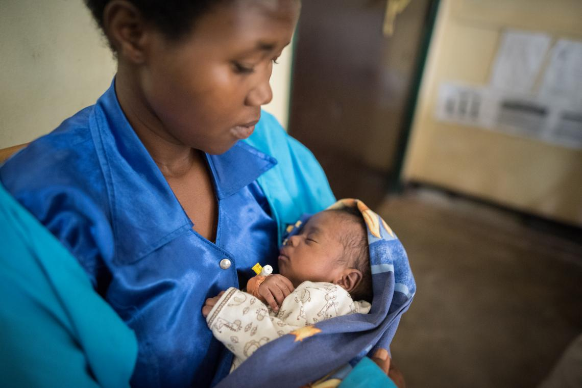 Mother and health worker in Rwanda hospital cradles baby
