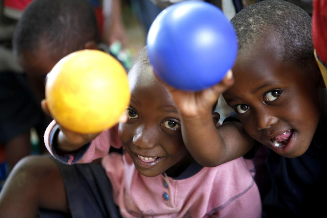 Two preschool children in Rwanda hold balls and small at camera