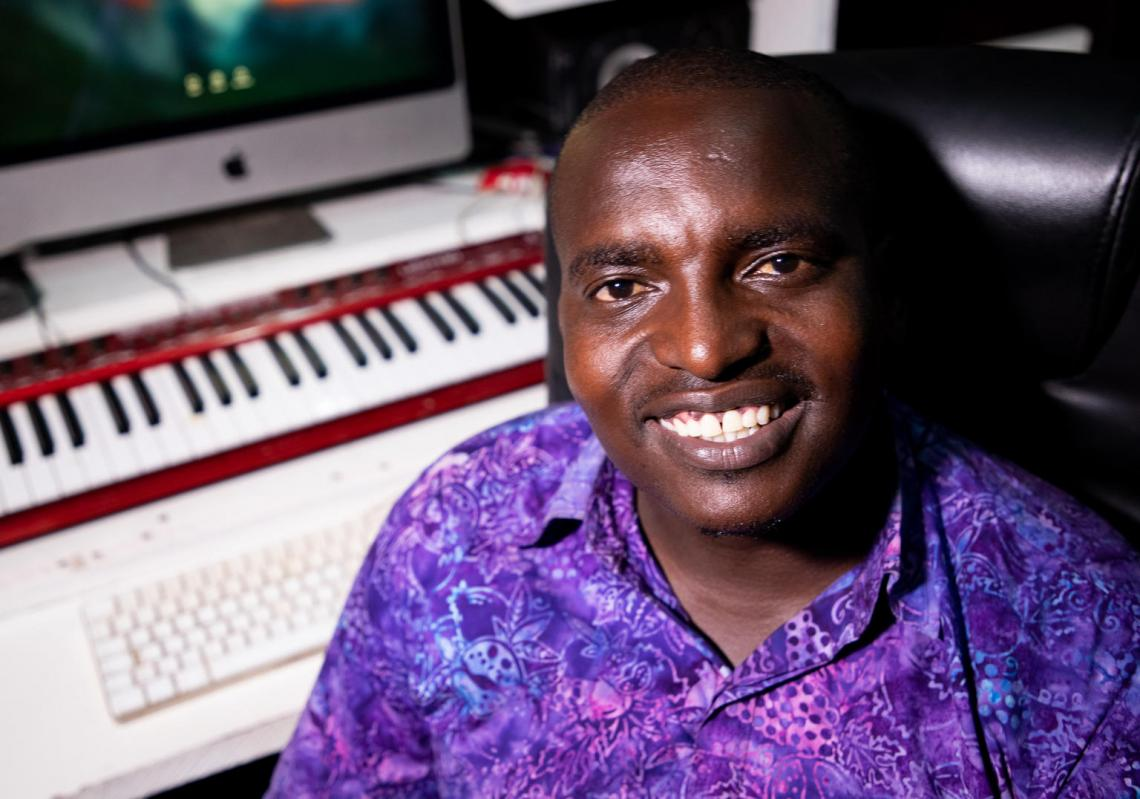 "Francois ""Sano"" Niyigena sits in his tiny one room radio studio, headphones around his neck, quickly moving between his laptop and his radio mic."