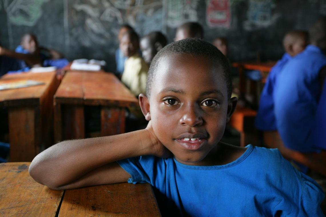 Primary school girl in Rwanda rests on desk