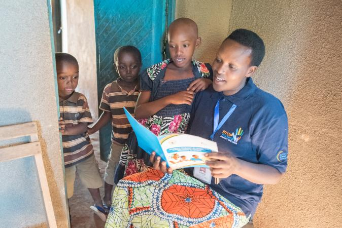 Woman with children in Rwanda reads education materials on violence against children