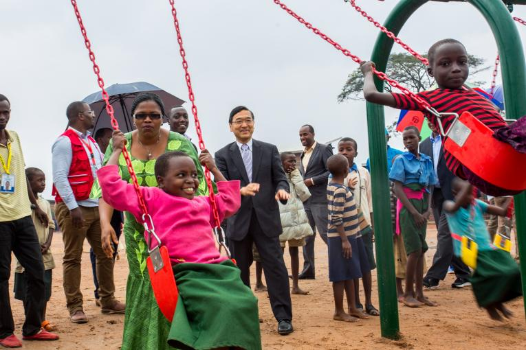 The Ambassador of Japan in Rwanda and the Rwandan Minister of Emergency management push children on a swing set in a refugee camp
