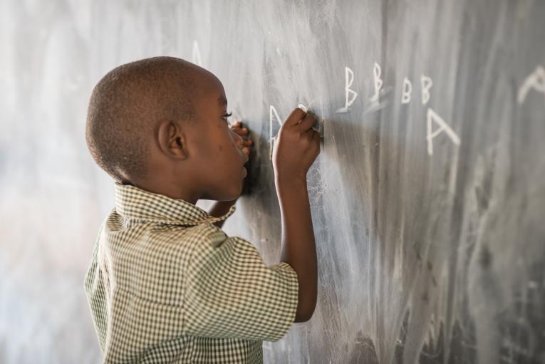 Boy in early childhood development centre writes on blackboard in Rwanda
