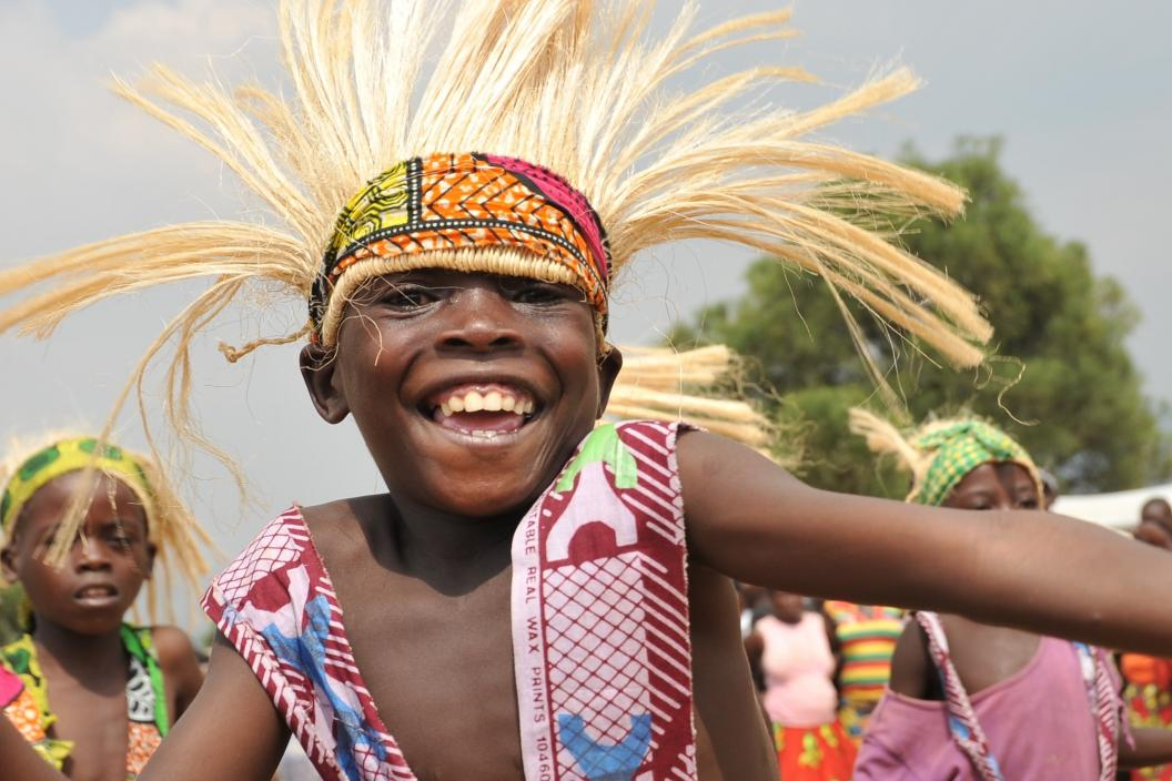 Rwandan boy wearing traditional intore dance costume smiles at camera in dynamic pose