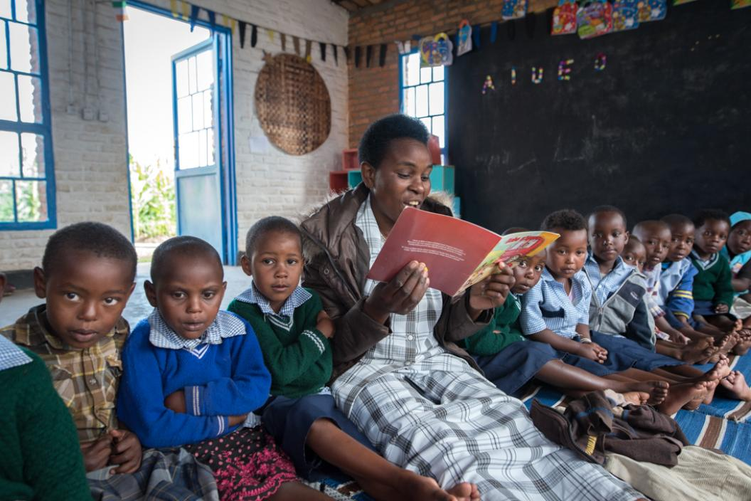 Teacher in preschool in Rwanda reads books to group of children