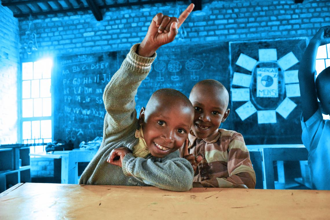 Two children in Rwanda raise their hands