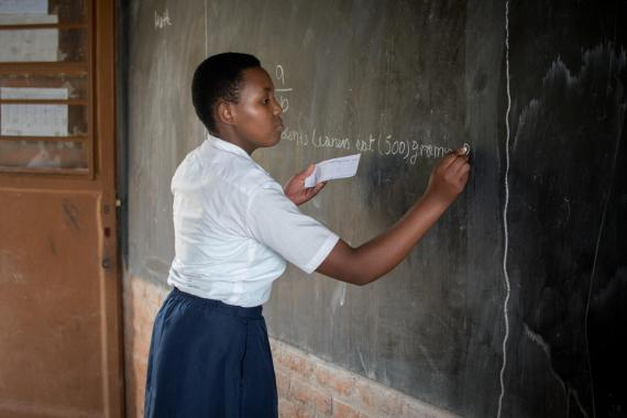 A young girl at a secondary school in Rwanda writes on the blackboard during a classroom activity.