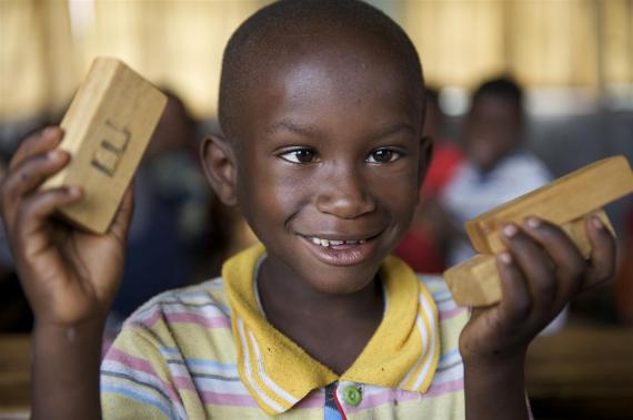A young boy uses blocks of wood to count in a Primary 1 classroom in Rwanda.