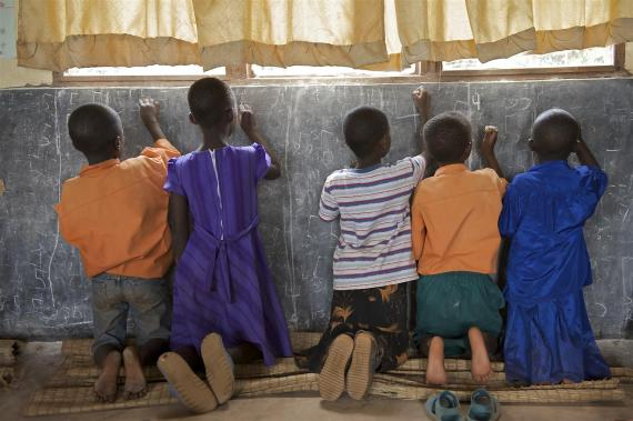 Children in a primary classroom in Rwanda practice writing the number 5 on a blackboard.