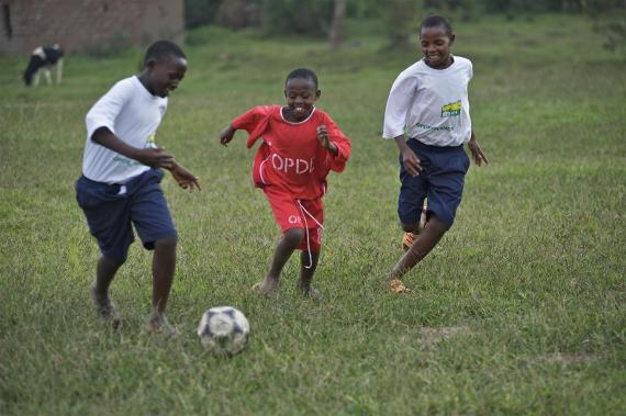 Children at a UNICEF-supported centre for street children play football together in Rwanda.