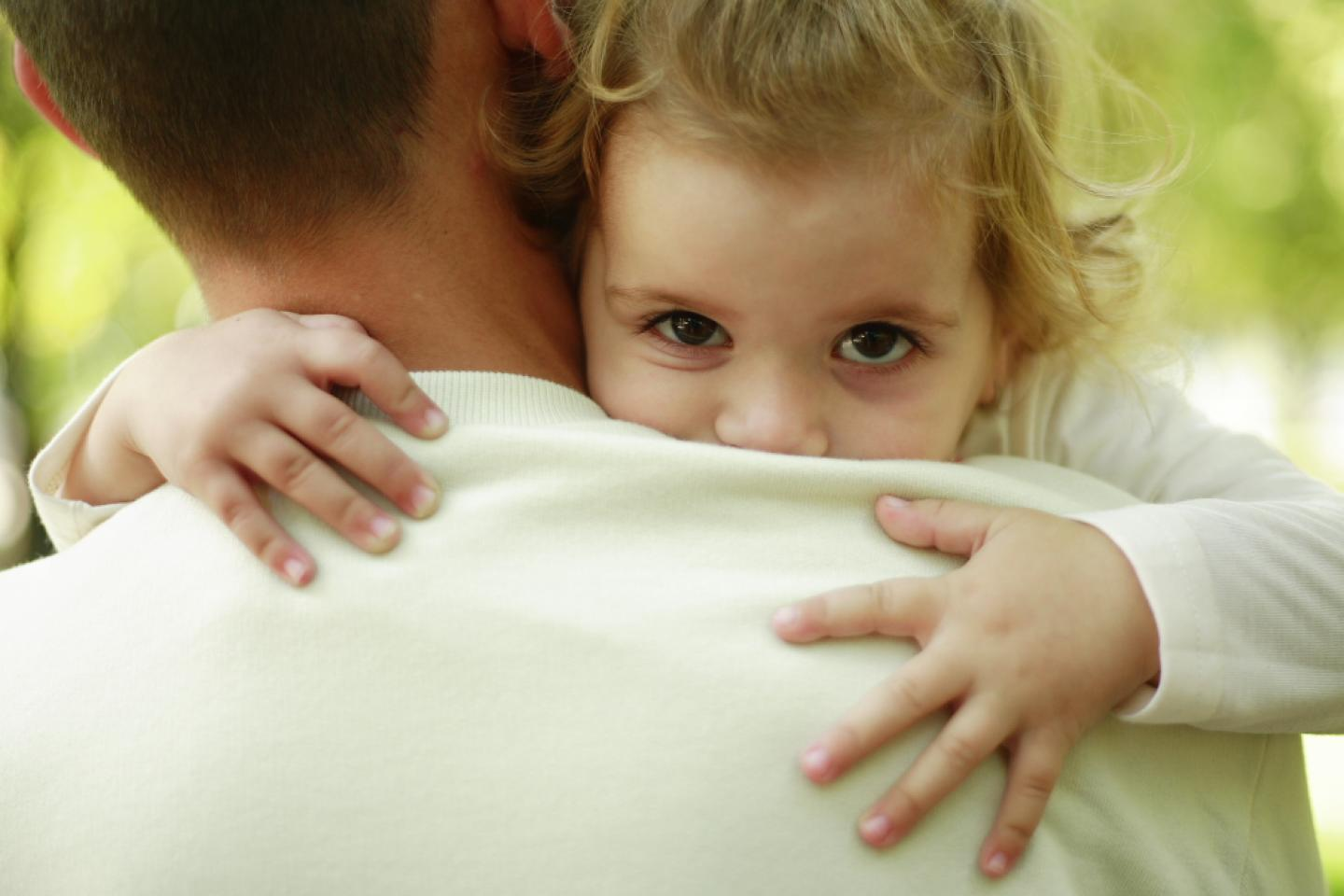 Father carries daughter in his arms while she hugs him