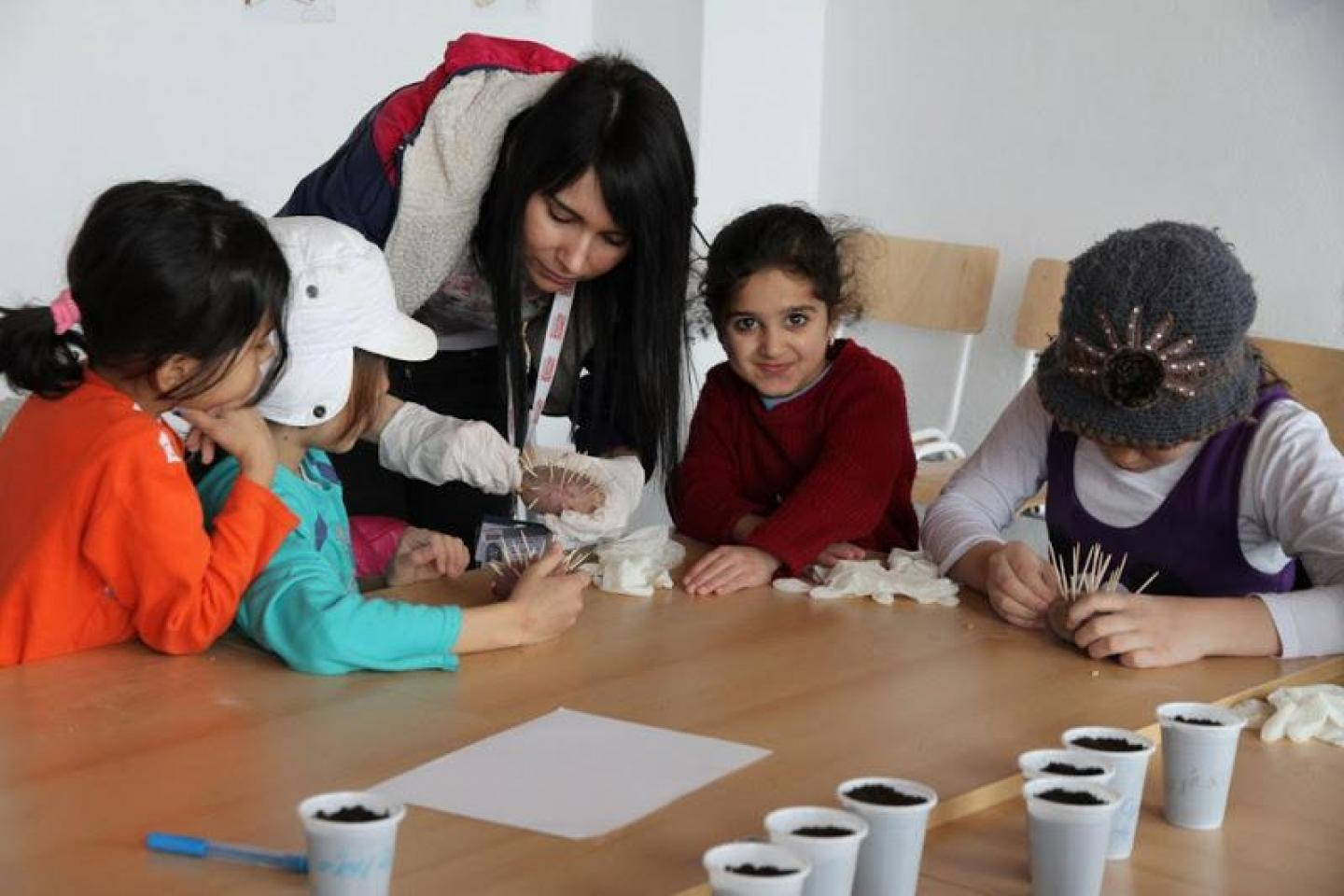 Children engaged in gardening activities in a spring-themed workshop in the One Stop Centre in Presevo, Serbia.