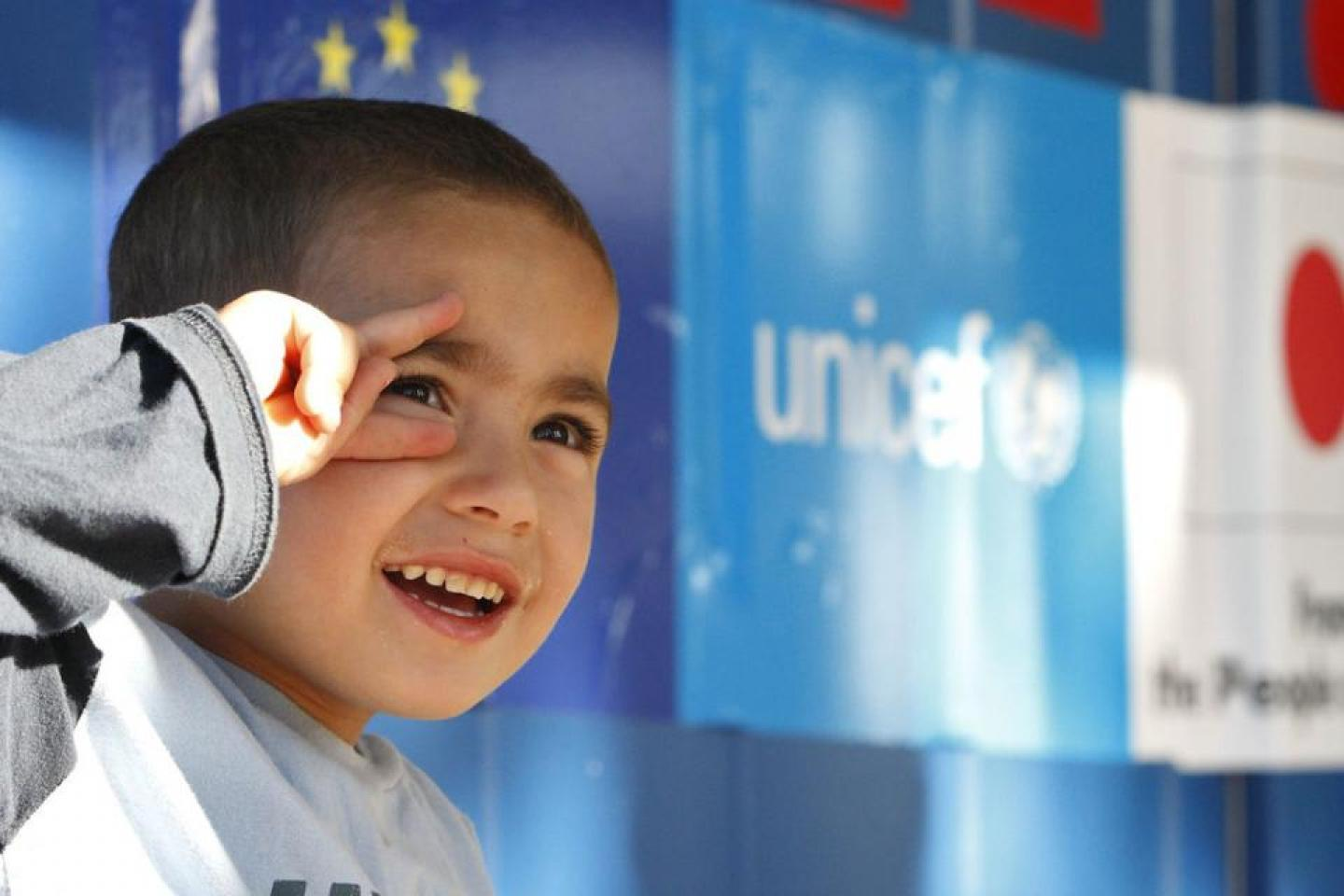 Child smiling and posing for a photo in front of the UNICEF and partners' banners