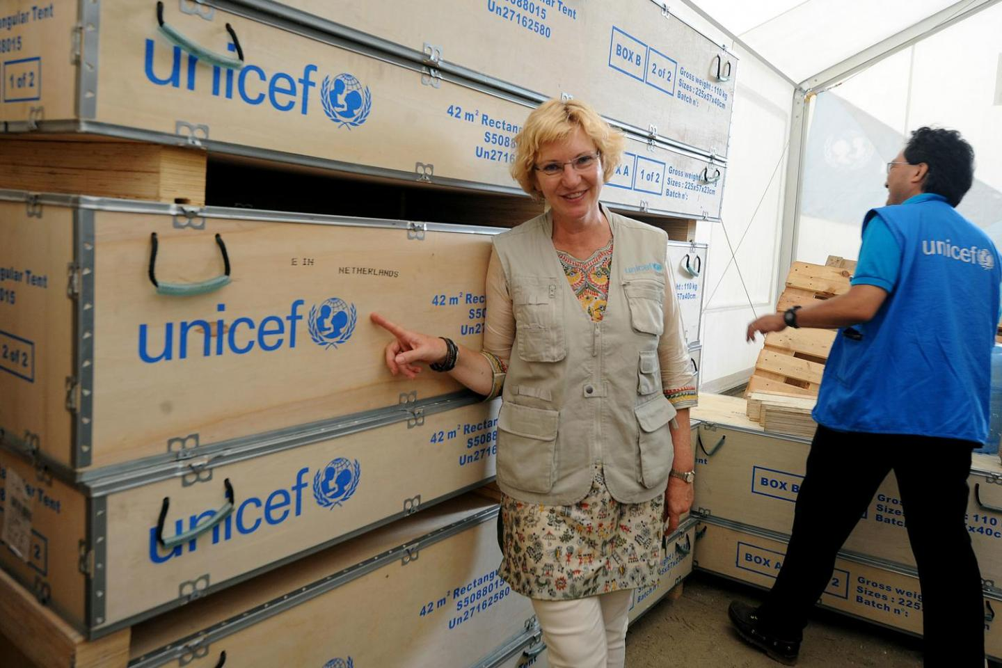 UNICEF ROSA Regional Director Karin Hulshof in fron of the boxes with tenst at the UNICEF Warehouse at the Tribhuvan International Airport. UNICEF Nepal Representative Tomoo Hozumi is also in the frame.