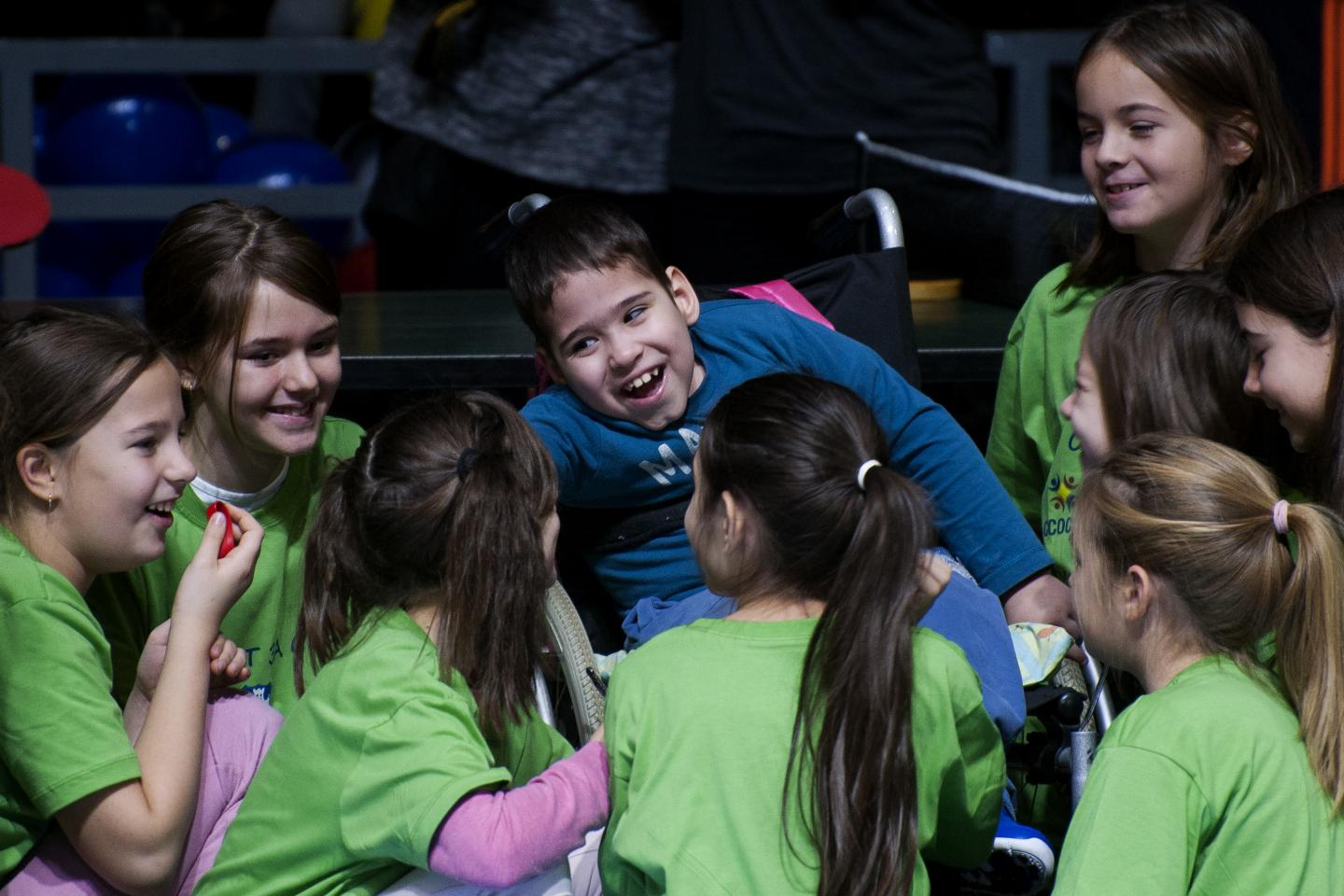 Boy with disability smiling with his friends at a sports event