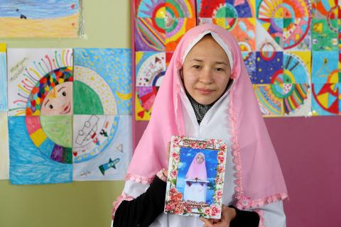 Nilufar (13) with the photograph and the headscarf she has with her wherever she goes