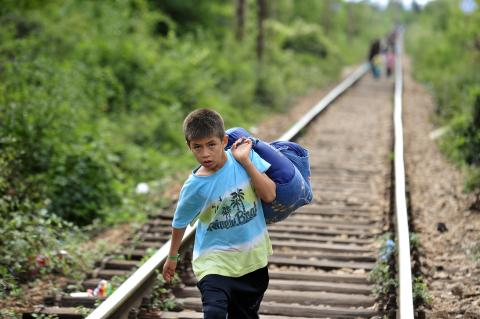 Refugee boy walking alone on a railway track
