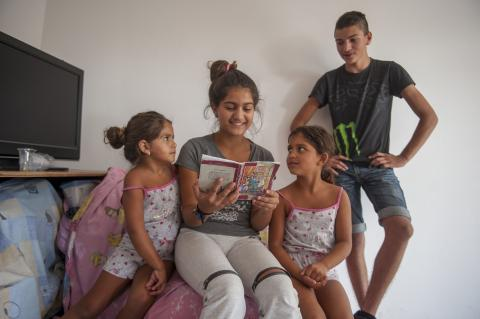Older sister Andjelina (12) and brother Arijan (14) read to their younger sisters Anastasija (7) and Elmedina (5)