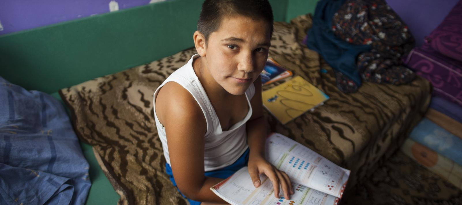 Roma boy, Aca, studying math from a school book