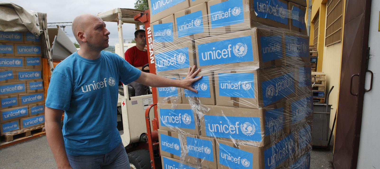 UNICEF worker with stacked goods during the emergency