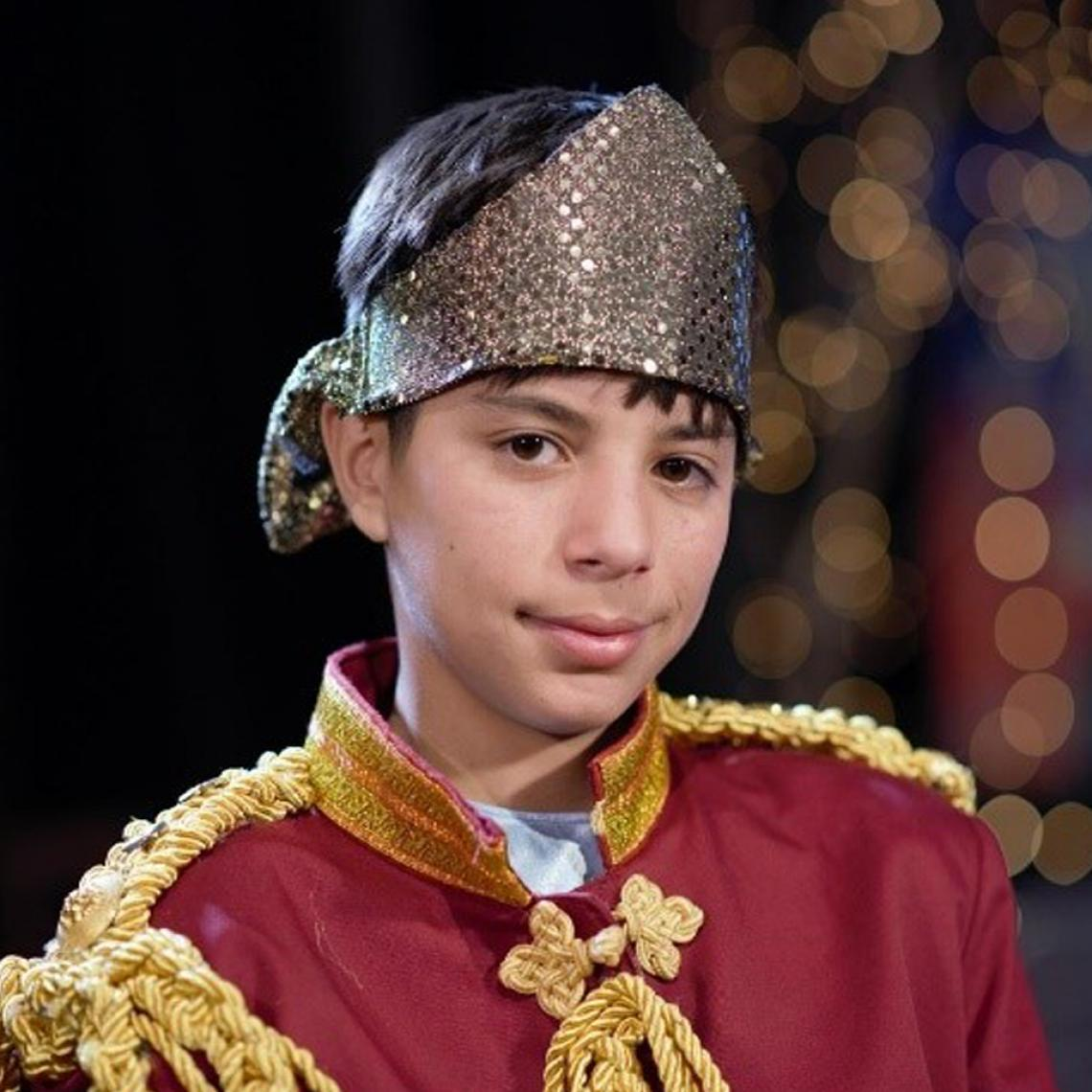 Muhammad (12) in a costume of a prince smiling at the camera.