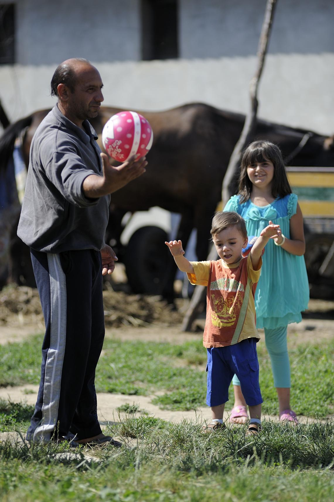 Zoran Jovanovic, playing with his children, David and Aleksandra, in the yard in front of the house.