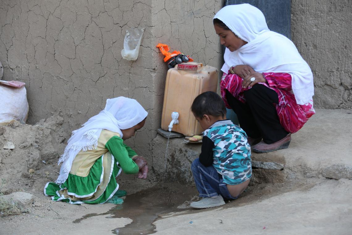 Mercia checks that her children are washing their hands properly outside their home in Nili District, central Afghanistan.