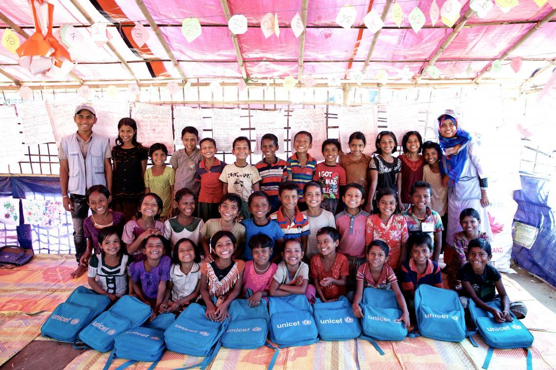 Rohingya refugees posing for a photo with their new school backpacks