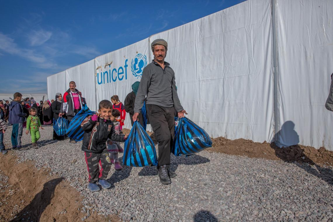 Muhammad (right) and his children leave a tent where they purchased winter clothes in Hasansham camp, Iraq.