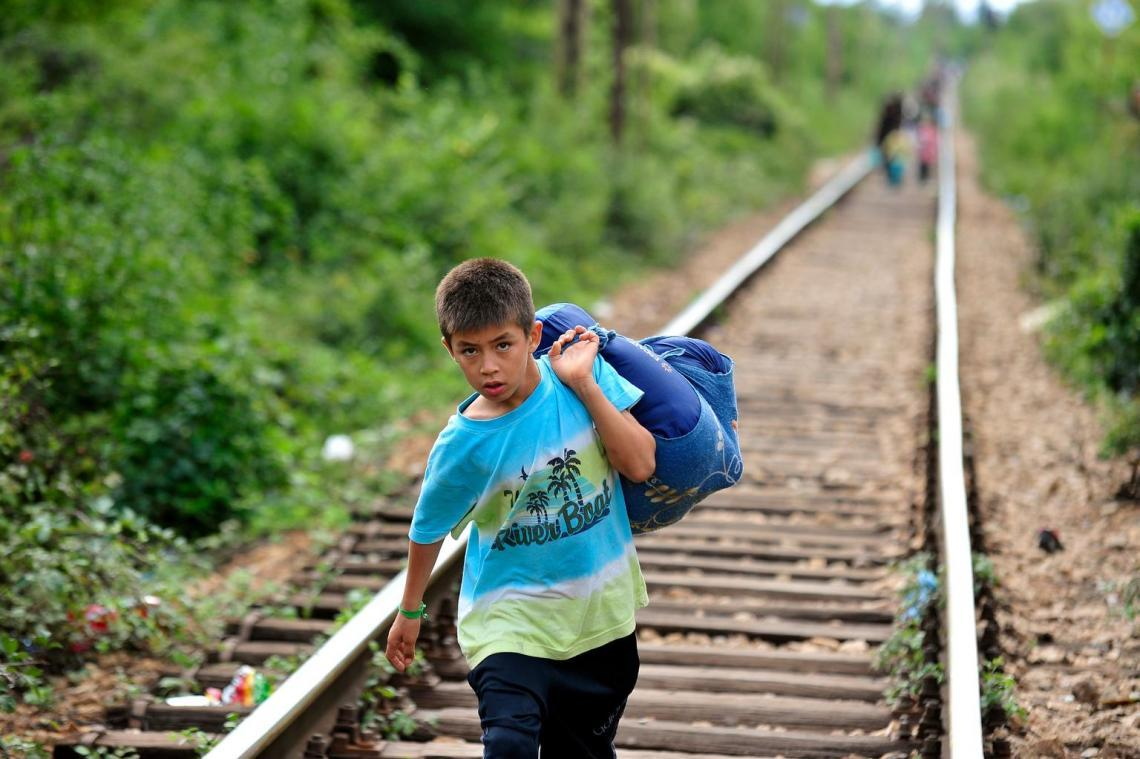 A boy carries his belongings in a large cloth bag as he walks on railway tracks to cross from the former Yugoslav Republic of Macedonia into Serbia.