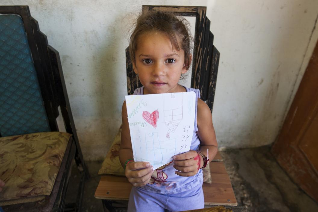 Roma girl holding a paper with her drawing of a red heart