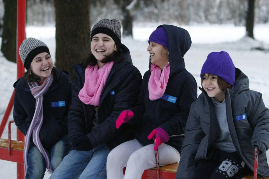 Refugee and migrant girls smiling at the refugee reception centre while wearing warm jackets provided by UNICEF and EU