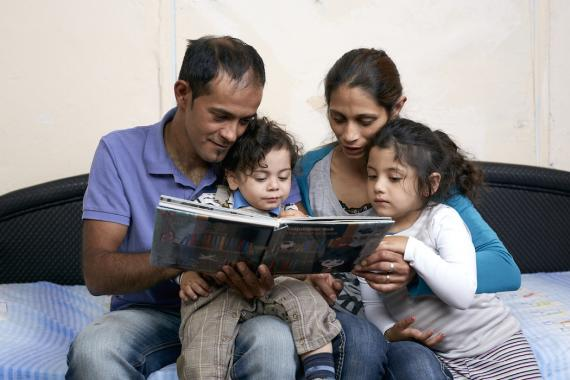 Roma mother and father reading a book to their son and daughter