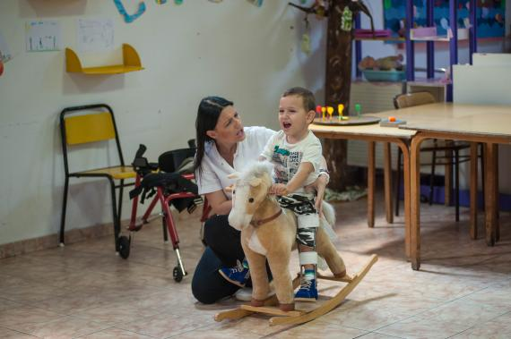 Boy with disability playing with his doctor and a wooden horse