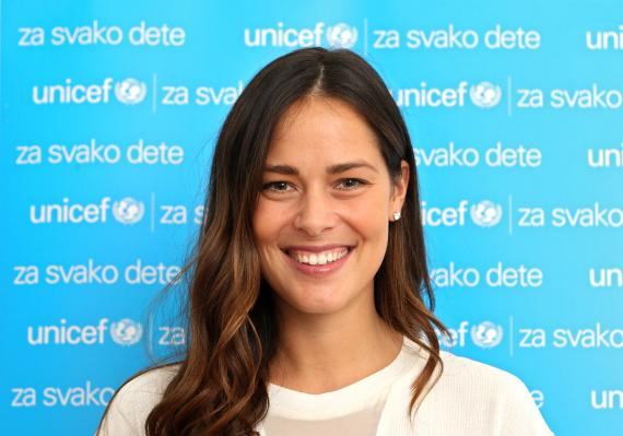 Ana Ivanovic smiling at the camera in front of the UNICEF banner