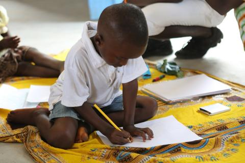 A child learns to write at an Early Childhood Development centre in Minthomore village, Port Loko District.