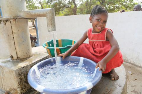 A girl squats by a bowl of water fetched from a community well provided by UNICEF.
