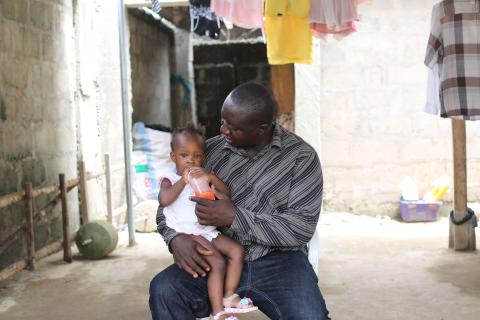 Yayah Bangura (a UNICEF staff) feeds his 19-month-old daughter Hafsa at their home in Freetown, before heading to work.