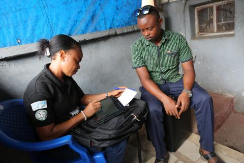 Fatmata Binta Jalloh, an interviewer in the ongoing Multiple Indicator Cluster Survey in Sierra Leone, interviews Alimamy Ali Hashim, at his business place in Freetown.