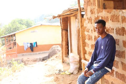 Bai (a young U-Reporter) sits by a house in his neighbourhood in Looking Town, western Sierra Leone.