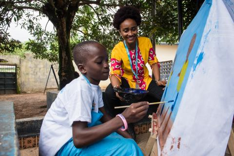 A child paints a drawing during an art session in Bo, southern Sierra Leone as UNICEF Communication Officer looks on.