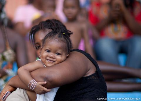 A mother carries her baby at the Siaka Stevens Stadium in Freetown.
