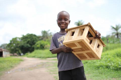 A boy carries a toy house, in Moyamba, southern Sierra Leone