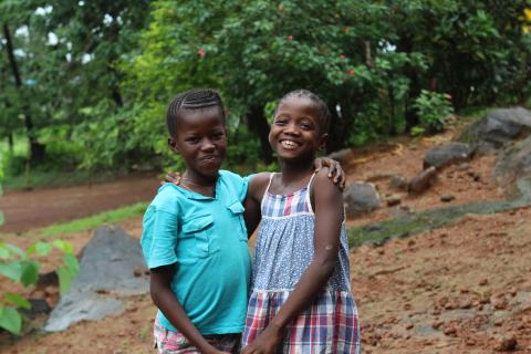 Two girls stand outside an orphanage in Grafton community, western Sierra Leone.