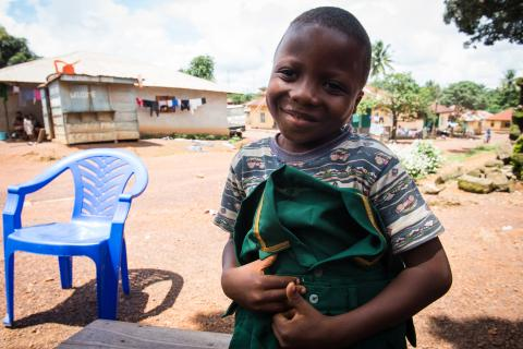 Six-year-old Lahai Charles shows off his pair of uniform outside his home in Kenema, eastern Sierra Leone
