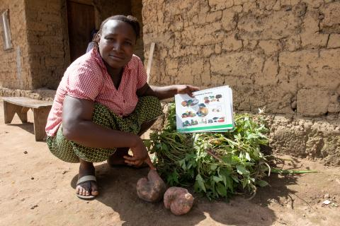 A member of a local Mother Support Group by a pile of crops harvested from her group'sgarden..
