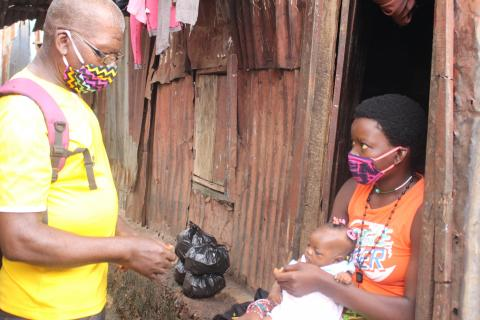 A Community Health Worker talks with a woman carrying a baby, in Freetown western Sierra Leone