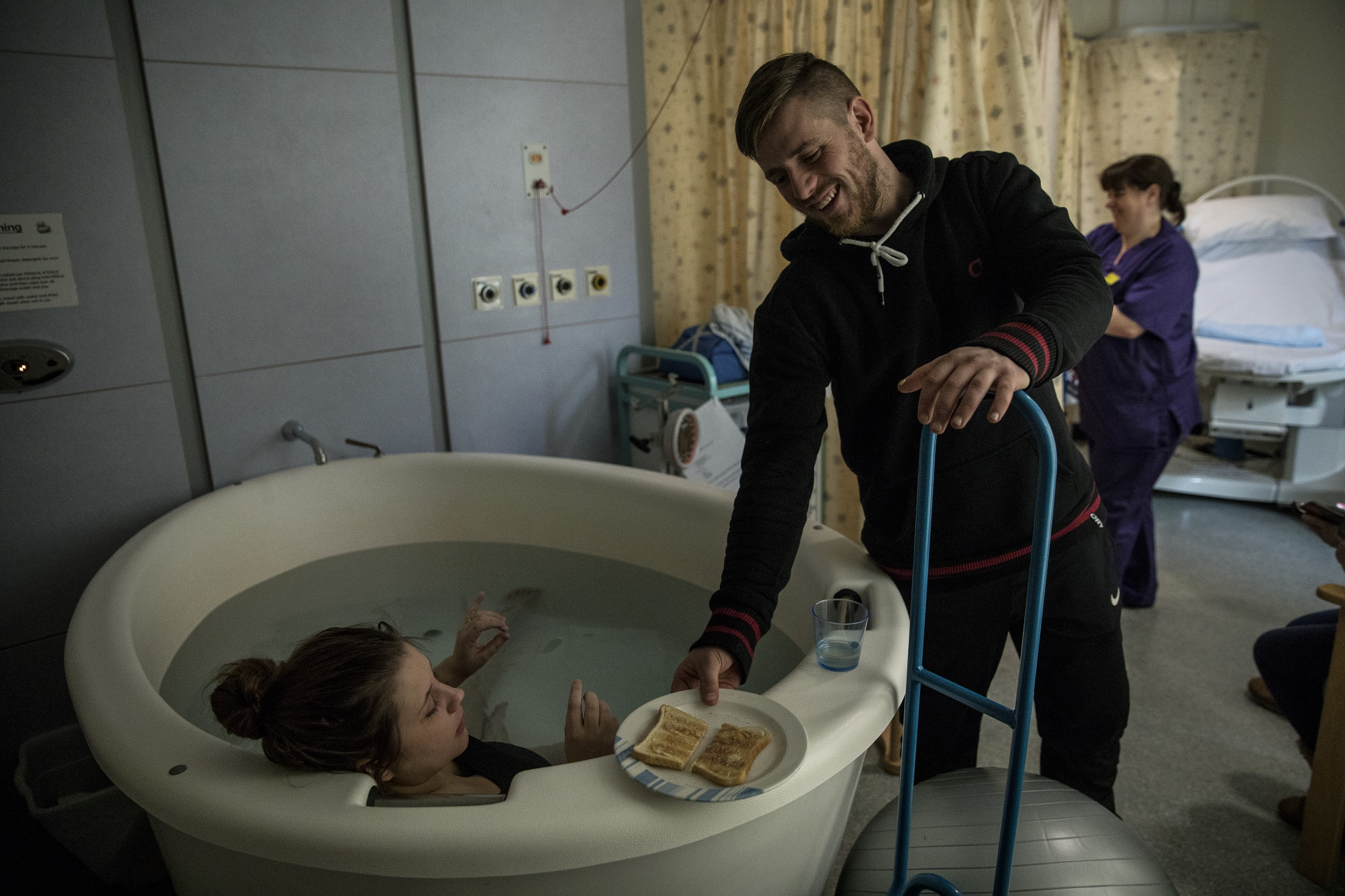 Damien Armes gives his wife Tamzin a piece of toast while she's in labour in a birthing pool, in the maternity ward of the Royal Devon and Exeter Hospital, in Exeter, Devon, England, 28 February 2018.