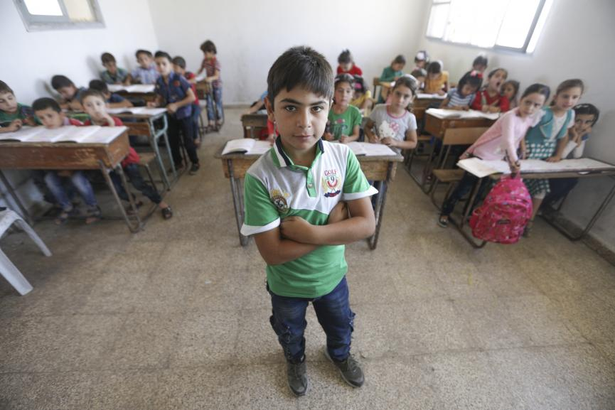 A boy stands at the front of a classroom, Syria