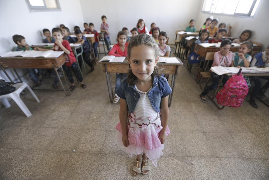 A girl stands in the front of a classroom, Syria